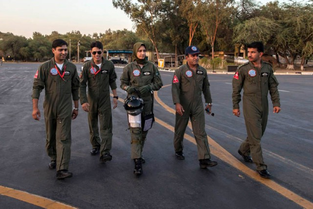 Ayesha Farooq, 26, Pakistan's only female war-ready fighter pilot, walks with Wing Commander of Squadron 20 Nasim Abbas and her colleagues toward a Chinese-made F-7PG fighter jet at Mushaf base in Sargodha