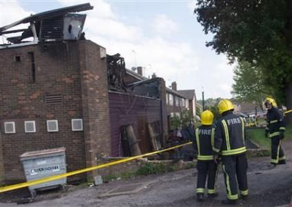 Firefighters stand next to the Al-Rahma Islamic Centre that was damaged by fire, in north London